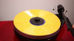 Close up view of a man cleaning yellow vinyl disc and putting down needle for playing record on audio record player stock video footage
