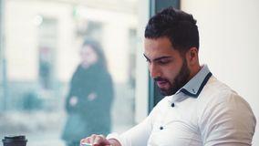 Close up view of a man drinking a coffee, checking his mail, smiling and texting back online. Online communication. Social networks. Having fun in a cafe stock video footage