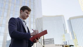 Close up view of man with folder on the city street. Young man with ring binder folder on urban landscape stock video