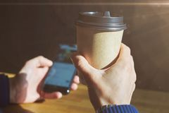 Close-up view of man hand holds a disposable paper glass, using smartphone while having rest drinks coffee in a sunny cafe. royalty free stock photo