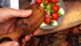 Close up view on man hand putting pepper into fresh cut vegetable bowl salad tomato pepper onion on wood board in forest stock footage