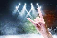 Close up view of man hand with rock gesture sign. Against concert spot lighting and smoke with defocused colorful lights background stock images