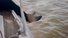 Close-up view of man legs lower out of the yacht. Businessman have a rest from work on the nature in sailboard alone. stock video