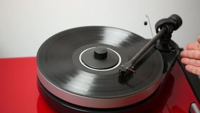 Close up view of a man lifting up needle on black vinyl disc on audio record player.