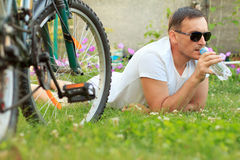 Close up view of man lying on green grass and drinking water fro Royalty Free Stock Photo
