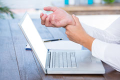 Close up view of man massaging his wrist. Over a laptop royalty free stock photography
