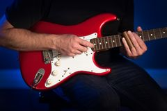 A close up view of a man playing a red and white electric guitar. royalty free stock photo