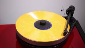 Close up view of a man putting down needle on yellow vinyl disc on audio record player.