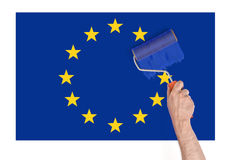 Close up view of man's hand painting over star on Europe Union flag Stock Photos