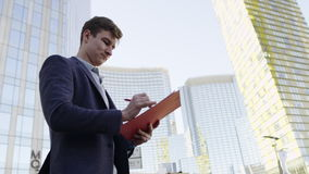Close up view of man taking notes in folder on the city street. Young man with ring binder taking notes in folder on urban landscape stock footage