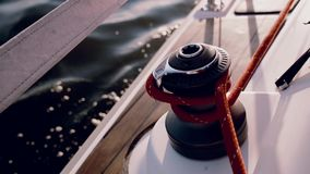 Close-up view of man using the capstan head to fixing the rope. Sailor using capstan drum, the crew steers the ship. Traveling by sea on the yacht in bright stock video
