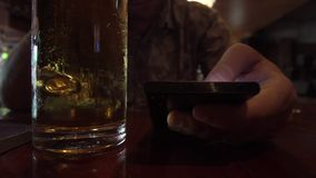 Close Up View of Man Using Samrtphone While Drinking Beer in Pub. Shot with a Sony a6300 fps29,97 4k stock video footage