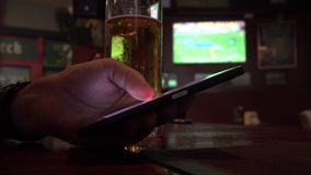 Close Up View of Man Using Samrtphone While Drinking Beer in Pub. Shot with a Sony a6300 fps29,97 4k stock footage