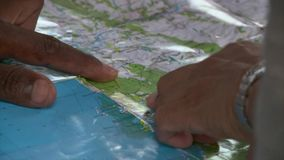 Close up view of man and woman pointing at places on world map royalty free stock image