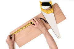 Close up view of a man's hands measuring wooden plank with tape line, isolated on white background Royalty Free Stock Images