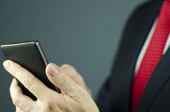 Close-up view of manager in suit with red tie holding smartphone with leather Royalty Free Stock Photos