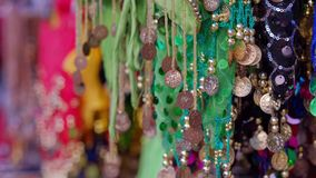 Close up view of many scarfs for a female belly dancers. 4K. 4K video. Arab scarfs with medallions of different flowers hang on east market of the old city of stock video footage