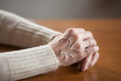 Close up view of mature female wrinkled hands on table stock photography