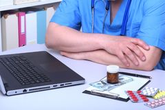 Close-up view of medical doctor working table. Laptop, stethoscope, assorted pils and patient information form. Healthcare and medical concept Royalty Free Stock Photo
