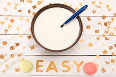Close-up view of milk and spoon in bowl, word easy from breakfast cereal letters. Macarons and alphabet corn flakes on wooden table Stock Images