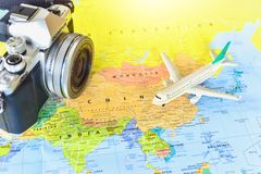 Miniature Airplane and Vintage Mirrorless Camera on World Map Background stock images