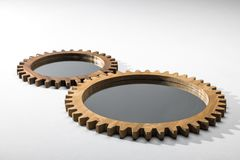 Close-up view of mirrors framed by wooden cogwheels. Lying on white Stock Images