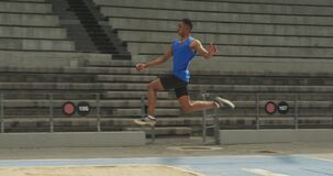 Close up view of mixed race athlete doing long jump