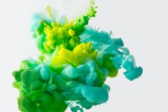 close up view of mixing of green, yellow and bright turquoise paints splashes in water isolated on gray stock photo