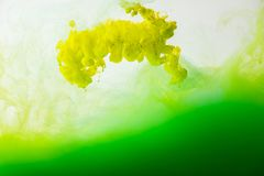 Close up view of mixing of paints splashes. Close up view of mixing of green and yellow paints splashes in water isolated on gray Royalty Free Stock Photo