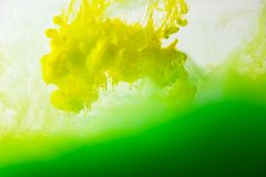 Close up view of mixing of paints splashes. Close up view of mixing of green and yellow paints splashes  in water isolated on gray Stock Image