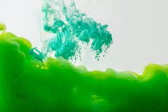 Close up view of mixing of paints splashes. Close up view of mixing of green and bright turquoise paints splashes in water isolated on gray Stock Image