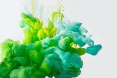 Close up view of mixing of paints splashes. Close up view of mixing of green, yellow and bright turquoise paints splashes in water isolated on gray Royalty Free Stock Images