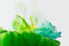 Close up view of mixing of paints splashes. Close up view of mixing of green, yellow and bright turquoise paints splashes in water isolated on gray Stock Images