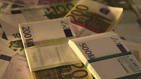 Close up view of money thrown down to desk in office. Several sums of euros are of various denominations put together in different stacks of thousands stock footage