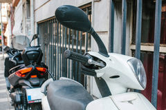 Close up view of motorized scooter parked on the sidewalk during daytime. Image of close up view of motorized scooter parked on the sidewalk during daytime Royalty Free Stock Image