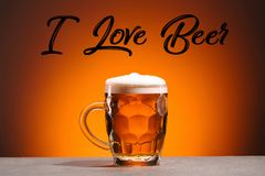 Close up view of mug of cold beer and i love beer lettering. On orange backdrop royalty free stock image