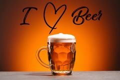 Close up view of mug of cold beer and i love beer lettering on orange backdrop royalty free stock images