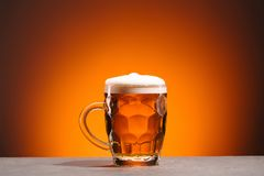 Close up view of mug of cold beer on orange backdrop royalty free stock photos