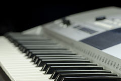Close-up view of a music keyboard with buttons and display on a blurred background. Close-up view of a music keyboard with buttons and display on a blurred black royalty free stock photo