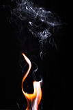 Close up view of natural flame with smoke. On black background Stock Photography