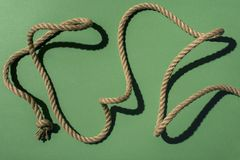 Close-up view of nautical rope with knots and shadow. On green stock image
