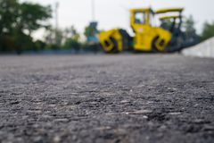 Close up view on the new asphalt road on which road roller is working. Construction site royalty free stock photos