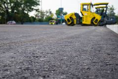 Close up view on the new asphalt road on which steamroller is working. Construction site. stock photos