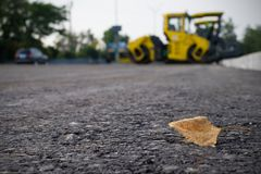 Close up view on the new asphalt road on which steamroller is working. Highway construction site stock photo