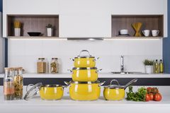 Close up view of nice cookware set with some vegetables on kitch. En in back royalty free stock photography