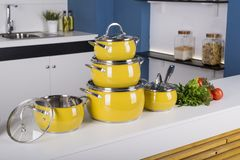 Close up view of nice cookware set with some vegetables on kitch. En in back royalty free stock images