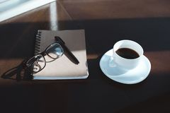 Cup of coffee and notebook. Close-up view of notebook with pen, eyeglasses and cup of coffee on table top royalty free stock image