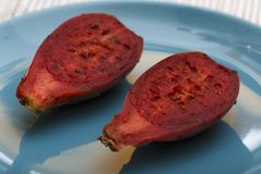 Free Close Up View Of Two Halves Of A Red Indian Fig Also Called Prickly Pear On A Blue Plate Royalty Free Stock Images - 157597539