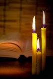 Close-up view of old burning candle with blurred old book on woo. Den background.  Education concept and Selective focus on tha candle with soft  light effect Stock Photography
