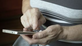 Close-up view on old female hands using smartphone. Close-up view on old female hands using smartphone at home stock video